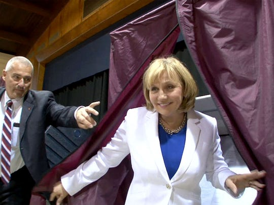 A state trooper holds the curtain open for Republican gubernatorial candidate and Lt. Gov. Kim Guadagno after she cast her vote in the primary at the Church of the Precious Blood Parish Center in Monmouth Beach on Tuesday.