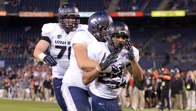 Utah State running back Joey DeMartino, right, celebrates with teammates after scoring in the fourth quarter against Northern Illinois at Qualcomm Stadium.