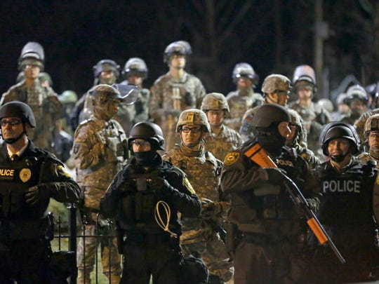 Police and Missouri National Guardsmen stand guard as protesters gather in front of Ferguson Police Department on Friday, Nov. 28, 2014. Tensions escalated late Friday during an initially calm demonstration after police said protesters were illegally blocking West Florissant Avenue.