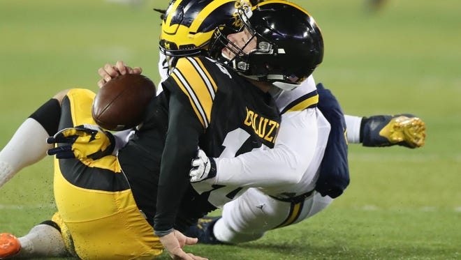Michigan's Devin Bush is called for targeting after this hit on Iowa punter Ron Coluzzi during first half action Saturday in Iowa City, Iowa.