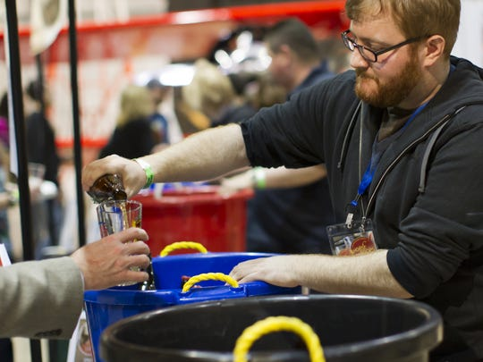 Mark Sarcone pours bottles of beer for New Belgium Brewing during the Hops and Props event in 2013. This year's event is March 3.
