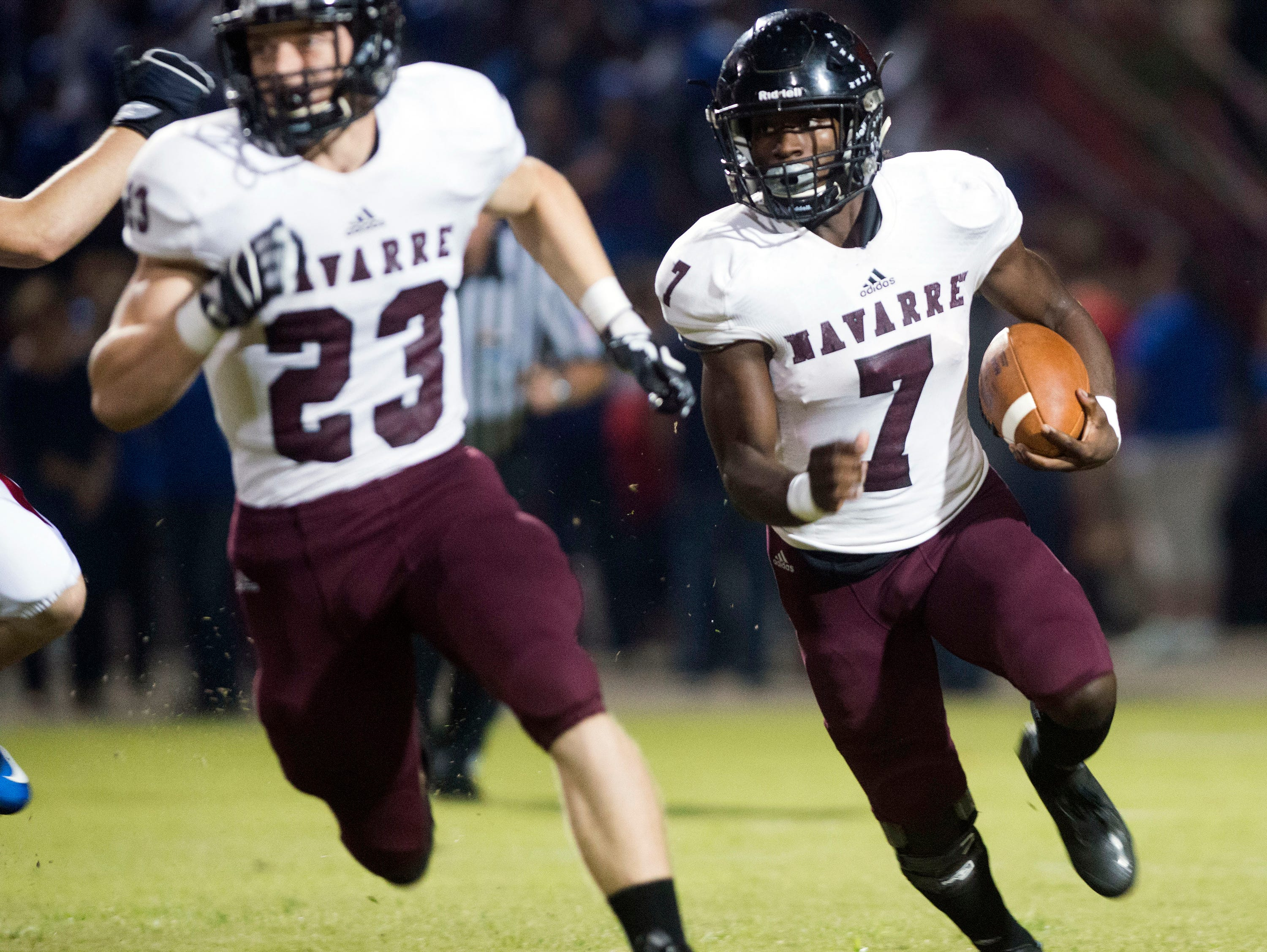 Navarre High School star running back Michael Carter (No. 7) runs for extra yards against the Pace High School defense with help from teammate, Chandler, Cooper, (No. 23) during Friday night's District 2-6A matchup.