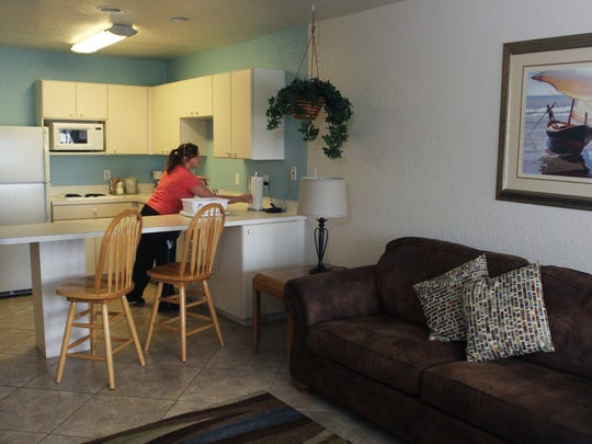 Housekeeper Kayla Barge, 24, cleans the kitchenette in a suite at the Legacy Harbour Hotel & Suites in Fort Myers.