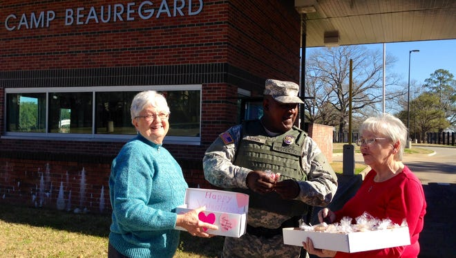 Local Ladies Auxiliary leaders Joyce Rose (left) and Linda Kieffer (right) offer homemade cookies and other Valentine's Day treats to Military Police Officer Sam Duskin at Camp Beauregard on Monday. The organization and its Junior Girls program deliver treats to Camp Beauregard, Esler Field and the VA Hospital every holiday and every two months.