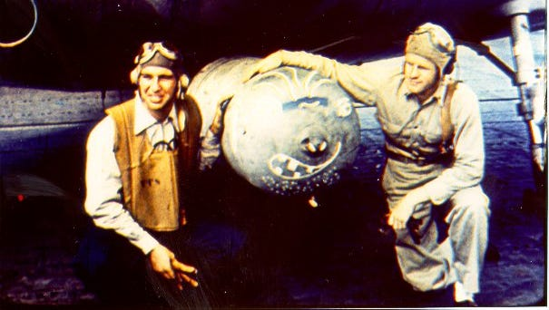 Bill Sawhill, at left, crouches in front his airplane on the deck of the aircraft carrier USS Hornet along with another member of his crew. (Photo courtesy of the Sawhill Family)