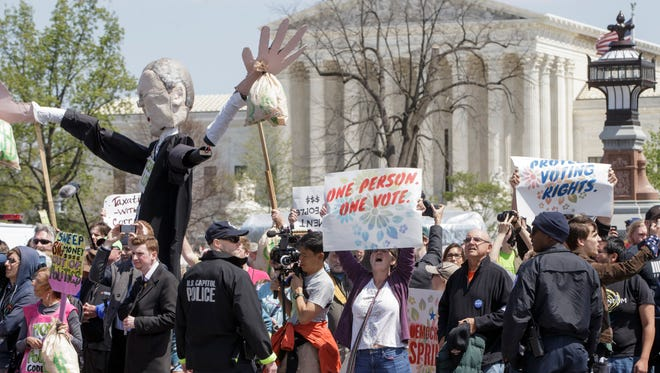 With the Supreme Court in the background, voting rights reform demonstrators stage a sit-in at the Capitol in Washington on Monday, urging lawmakers to get money out of the political process. About 400 people, including some from Delaware, were arrested.