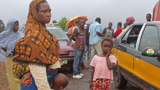 In this photo taken on Tuesday, Aug. 12, stranded people stand at a  roadblock  that separates Guinea and Sierra Leone, and works as a makeshift border control checkpoint at  Gbalamuya-Pamelap, Guinea. As Guinea closed its border with Sierra Leone over the weekend in an attempt to halt the spread of the deadly Ebola virus, people and goods were not able to cross to either side.