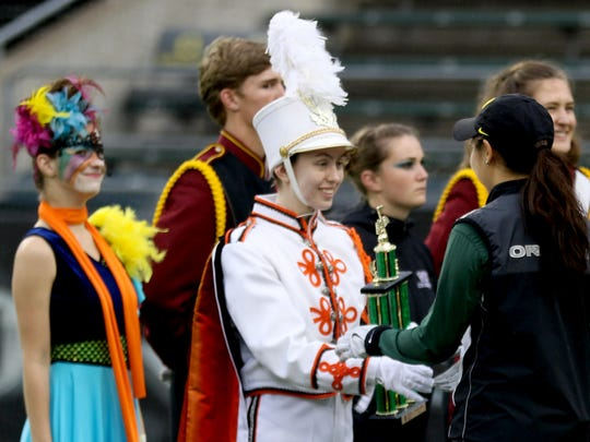A Sprague marching band representative accepts the second place trophy for Class A during the preliminary awards ceremony for the NWAPA marching band championships at Autzen Stadium in Eugene on Saturday, Oct. 31, 2015.