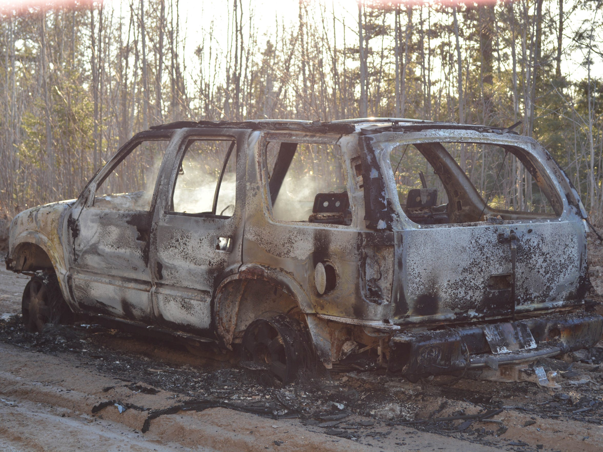 The burned Bravada containing the bodies of tripple homicide victims Heather Aldrich, Carrie Nelson and Jodi Hutchinson lies in the traffic lane of River Road just outside Manistique in mid April 2015.