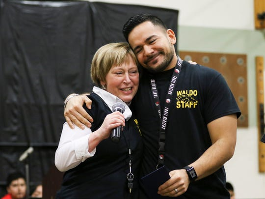Waldo Middle School teacher Ricardo Larios embraces Principal Tricia Nelson as he is awarded the prestigious Milken Educator Award on Wednesday, Jan. 6, 2016, in Salem. The award was kept a surprise from the school and its administration until the special assembly.