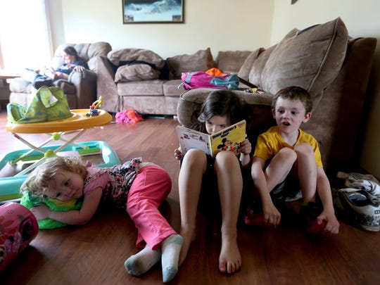 Melody Reitzer, 6, reads a book out loud for two of her siblings, Destiny Reitzer, 2, and Chance Davenport, 5, at her stepfather's home in Salem on Wednesday, April 20, 2016. Melody, her mom and three siblings live at the Simonka Place women's and children's shelter in Keizer.