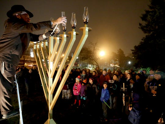 Rabbi Avrohom Perlstein lights the menorah during a ceremony on the fifth night of Hanukkah in downtown Salem in 2016.
