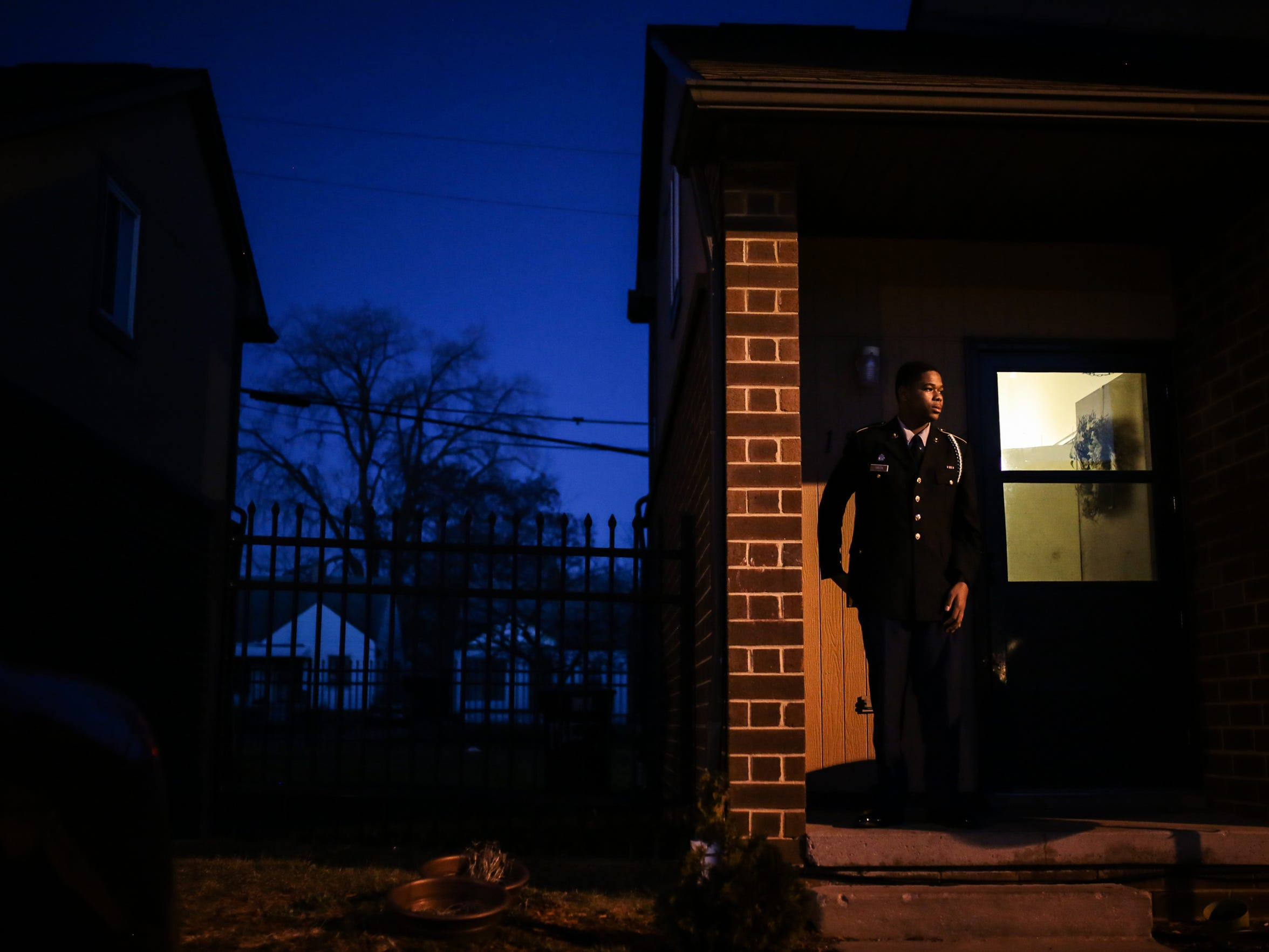 Myles Green, 15, stands on his porch in the darkness of a late winter's evening on March 7, 2017 while wearing his JROTC uniform. He lives with his mother and sister in the Sojourner Truth Housing Project on Detroit's east side. It's the last stop of the day for the Salvation Army's Bed and Bread program food truck.