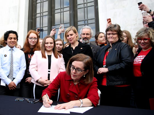 """Gov. Kate Brown signs HB 4145 at the Oregon State Capitol in Salem on Monday, March 5, 2018. The law expands the prohibition of owning a gun to people convicted of domestic violence, closing the """"intimate partner loophole"""" and blocks people convicted of misdemeanor stalking from gun ownership."""