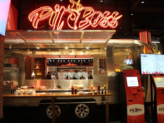 At Monroe Market, Pit Boss neon sign beckons hungry patrons to an Airstream-style trailer that turns out pulled pork, smoked chicken and more.