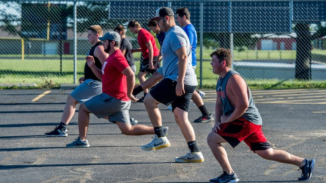 Metamora football players warm up in the parking lot before a summer workout last month at the high school.