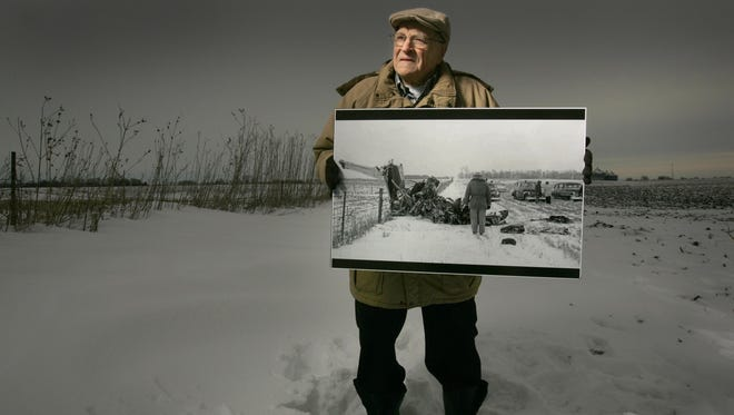 "Former Mason City Globe Gazette photographer Elwin Musser holding photo he took Feb. 3, 1959 at the spot of the plane crash north of Clear Lake that claimed the lives of rock 'n' roll musicians Buddy Holly, Ritchie Valens, and J. P. ""The Big Bopper"" Richardson and pilot Roger Peterson."