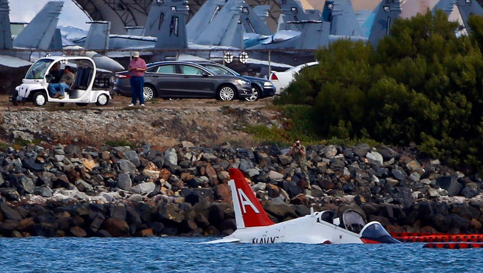 A Navy aircraft sits in shallow water in San Diego