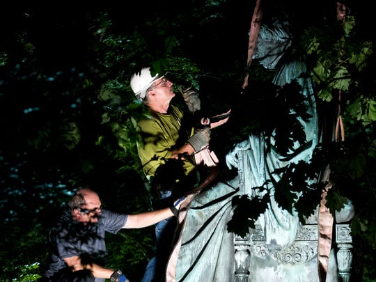 Workers remove a monument dedicated to U.S. Supreme Court Chief Justice Roger Brooke Taney from outside the Maryland State House, in Annapolis, Md., early Friday, Aug. 18, 2017. Maryland workers hauled several monuments away, days after a white nationalist rally in Charlottesville, Virginia, turned deadly.