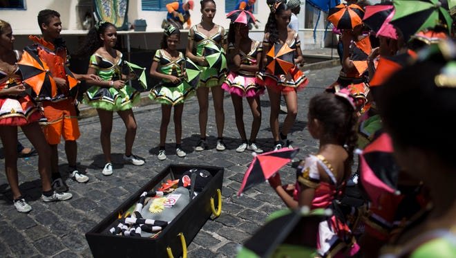 """Young revelers stand around a coffin containing an Aedes aegypti mosquito puppet during the """"Burial of the Mosquito"""" carnival block parade in Olinda, Pernambuco state, Brazil,  Feb. 5, 2016. The parade that happens every year during carnival underscores the dangers of the mosquito, carrier of the Zika virus."""