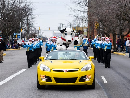 The Christmas Parade makes its way down Center Street on Saturday afternoon with the River Valley Marching band performing christmas songs.
