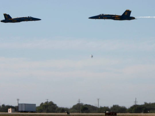 Two F/A-18 Hornets from the Blue Angels perform a maneuver during the Point Mugu Air Show in 2015.