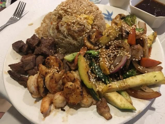 Oh Toi Asian Restaurant's steak and shrimp hibachi comes with grilled mixed veggies next to a scoop of fried rice and a pile of filet and shrimp.
