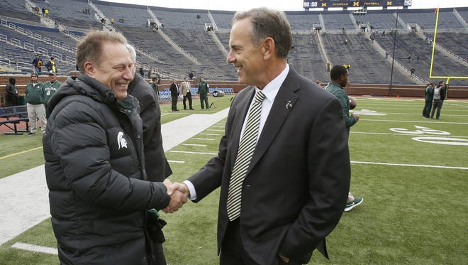 Michigan State basketball coach Tom Izzo greets football coach head coach Mark Dantonio on the field at Michigan Stadium before their football game against Michigan on October 17.