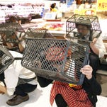 Employees of a supermarket cover their heads with shopping baskets during an anti-disaster drill in Kobe, western Japan, Thursday, Jan. 14, 2016.