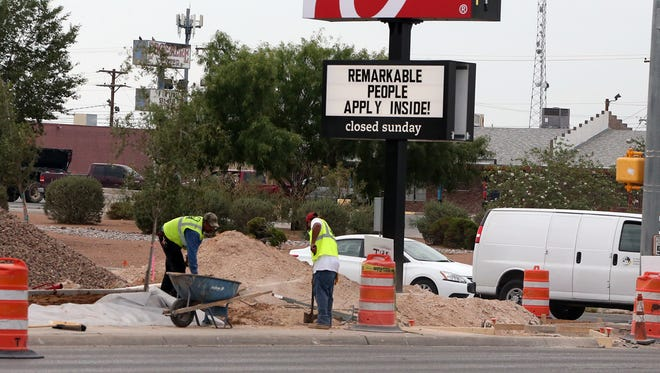 Workers do landscape work Tuesday outside a new Chick-fil-A restaurant at Airway and Edgemere boulevards. Airway is experiencing a renaissance with a variety of new businesses popping up there. It also is home to a number of car dealerships.