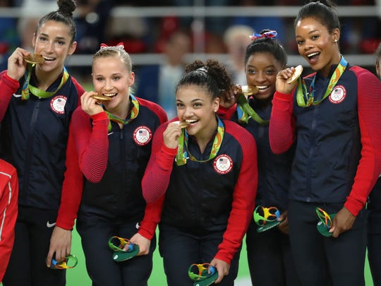 From left, Alexandra Raisman, Madison Kocian, Lauren Hernandez, Simone Biles and Gabby Douglas celebrate on the medal stand on August 9, 2016, at the Rio Olympic Games in Rio De Janeiro, Brazil. The U.S. women's squad captured the gold medal in the team competition.