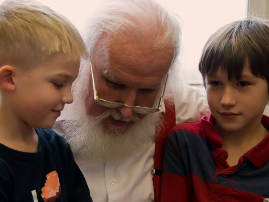 Santa Claus chats with a couple kids during a recent