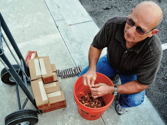 Jay Sperry of Palm Bay prepares his pennies to pay a code enforcement fine.