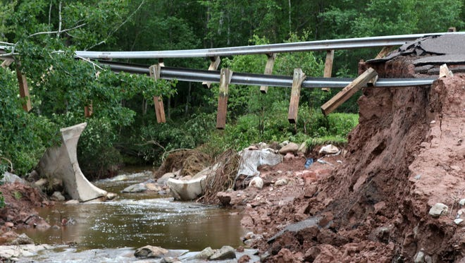 Guardrails are suspended after floodwaters took out part of Iron County A in Saxon, just north of Saxon Harbor, July 14, 2016.