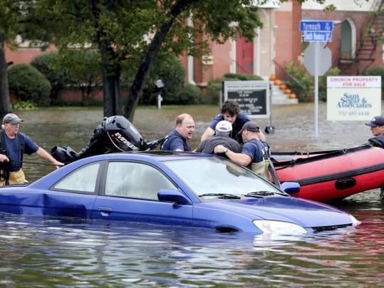 Members of Norfolk Fire-Rescue pull a man from his car stranded because of flooding in Norfolk, Va., on Sunday, Oct. 4, 2015. (AP Photo/Jason Hirschfeld)