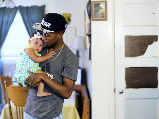"Shannon Brabham holds his daughter, 9-month-old Alaya Brabham, at his home in York. Brabham, who is about to release his 10th EP, writes about fatherhood and families in his song ""Pressure."""