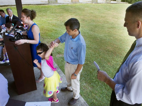 From the left, Angie Sharrer speaks at a press conference while her daughter Annie, 10, dances with her father Matt, all of New Oxford. U.S. Rep. Scott Perry is at right. Annie has been treated with a dozen medications unsuccessfully, one sending her to Hershey due to complications.