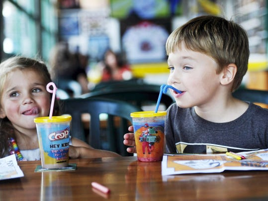 Audrey Guerrini, 4, and Andrew Guerrini, 6, of York Township sip drinks through twisty straws at Quaker Steak and Lube.
