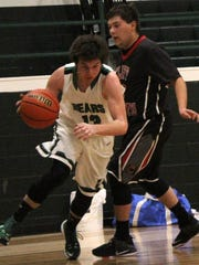 Cloudcroft's Kasen Flotte, left, dribbles past Cliff's Tyler Barnwell on Friday night.
