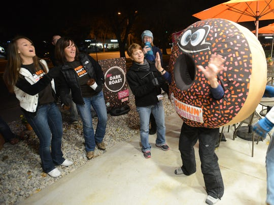 Customer, Judy Tessier, right, entertains others by putting on the donut suit as they wait for the Dunkin Donuts to open on the grand opening  early Tuesday morning Oct. 28, 2014.