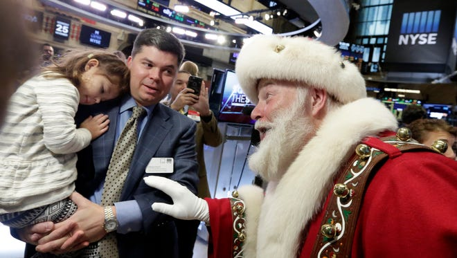 Piper Foley, 4, daughter of New York Stock Exchange Senior Vice President Douglas Foley, meets Santa Claus from the Macy's Thanksgiving Parade, on the floor of the New York Stock Exchange before the opening bell Wednesday, Nov. 25, 2015.