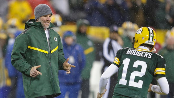 Green Bay Packers quarterback Aaron Rodgers (12) greets Brett Favre on the field after Favre's number was retired at halftime against the Chicago Bears at Lambeau Field.