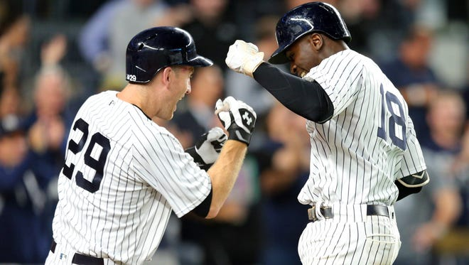 New York Yankees shortstop Didi Gregorius (18) celebrates his solo home run against the Cincinnati Reds with New York Yankees third baseman Todd Frazier (29) during the eighth inning at Yankee Stadium.