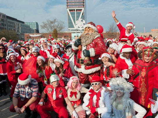 A crowd of people dressed as Santa gather for a group