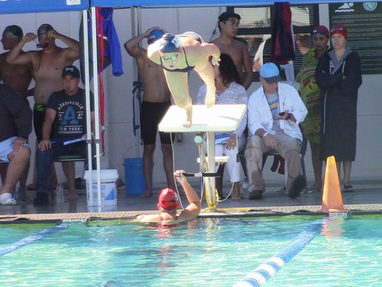 Estero's Mikayla Puckett dives in as she competes in