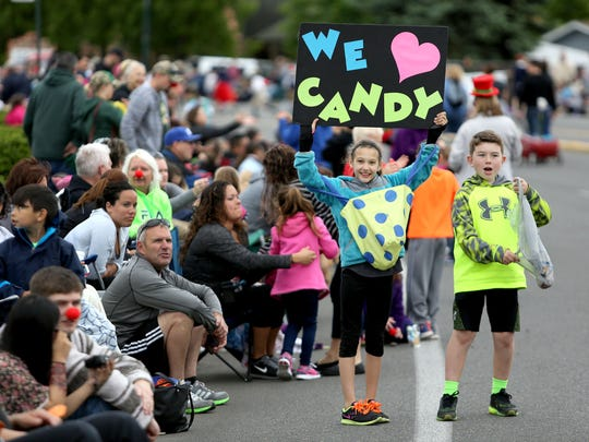 Sadie Sell, 9, and her friend Ronan Snyder, 9, stand along River Road N in Keizer during Saturday's Iris Festival Parade.