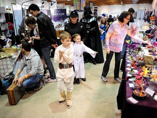"""""""Star Wars"""" family of Keizer — Lucian Bader, 7; Lucinda Bader, 6; Jekka Lopez; and Shawn Bader — walk through the booths Sunday during Cherry City Comic Con at the Oregon State Fairgrounds."""