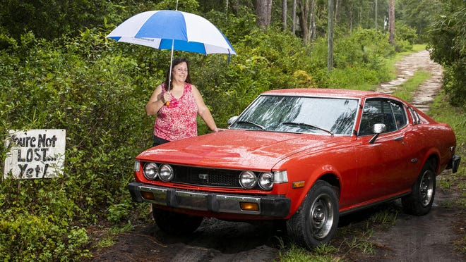 "Julie Mancini poses with her 1977 Toyota Celica GT Liftback on July 28. "" I had one when I was a kid. I think I got mine when I was 18,"" she said while standing on the driveway to her parent's home in Dunnellon. ""I made the sign (You're Not Lost Yet!) when I was in high school. My dad said to make it for my friends who would come to the house."""