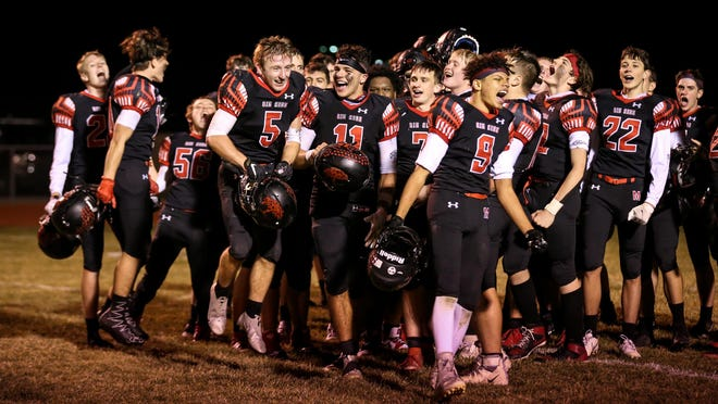 Milan's football team celebrates a playoff win over Airport on Nov. 6.