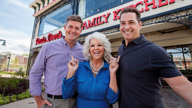 Paula Deen and her sons pose for a photo in front of Paula Deen's Family Kitchen in Pigeon Forge, Tennessee.